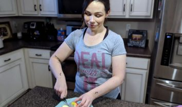"""Bluegrass Blogger stands in her kitchen, wearing a grey athletic t-shirt that reads """"Deal With It"""" in pink, cursive writing. She is slicing a healthy, red apple on a small, teal plate."""