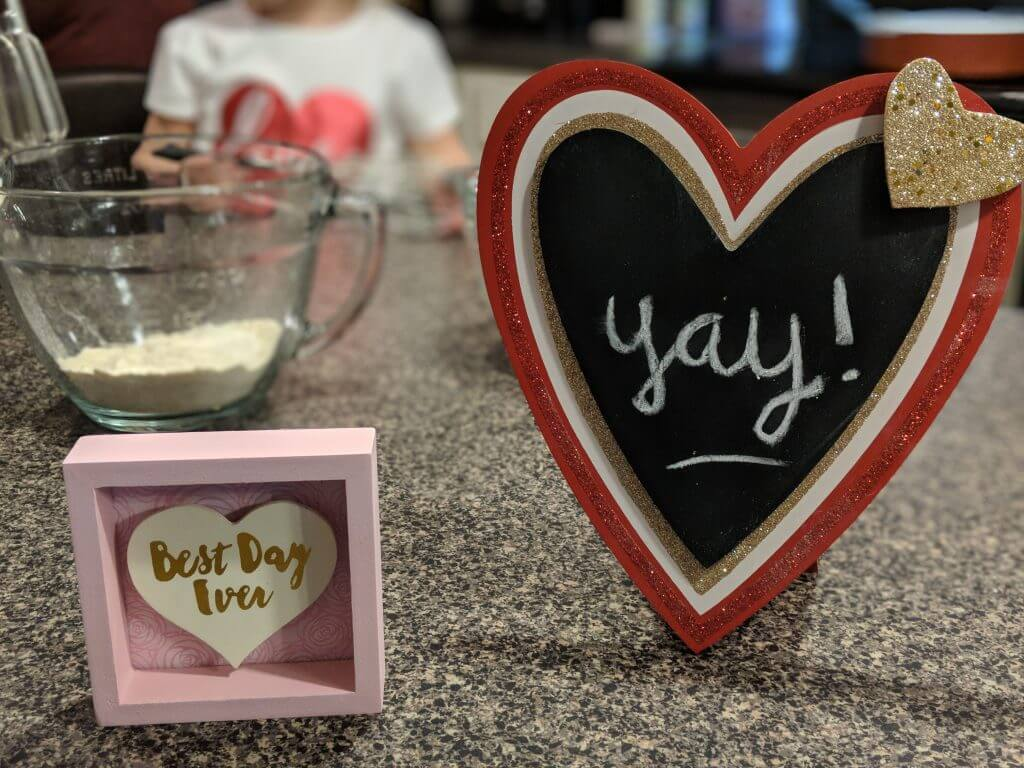 "In the background a glass bowl of dry pancake mix sits on a kitchen counter. In the foreground a small, pink frame contains a white heard and text written in gold foil that says ""Best Day Ever"" in cursive script. Beside it sits a red, glitter heart frame with a black chalkboard in the center. On the chalkboard the word ""yay!"" is written in cursive writing."