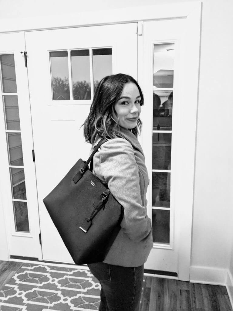 Black and white photo of Bluegrass Blogger (Christine) looking over her shoulder as she walks towards the front door of her home. She is wearing a light colored, fitted coat and a large, black tote bag on her shoulder. The picture is a part of a blog post that explains how your job can turn you into your best self.