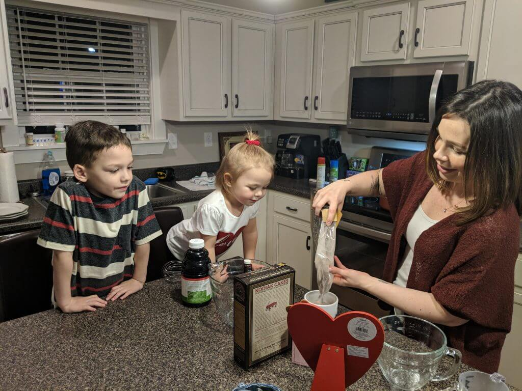 Christine, aka Bluegrass Blogger, pours dry pancake mix into a bowl while her two children eagerly look on.