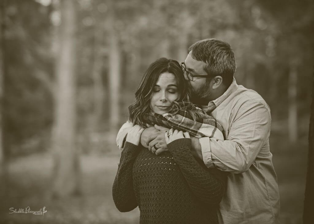 How To Support Someone With Anxiety: Christine (the Bluegrass Blogger) and her husband embrace. He is standing behind her, his arms wrapped around her shoulders and he is kissing the side of her head. Her eyes are closed and her hands lay on top of his.