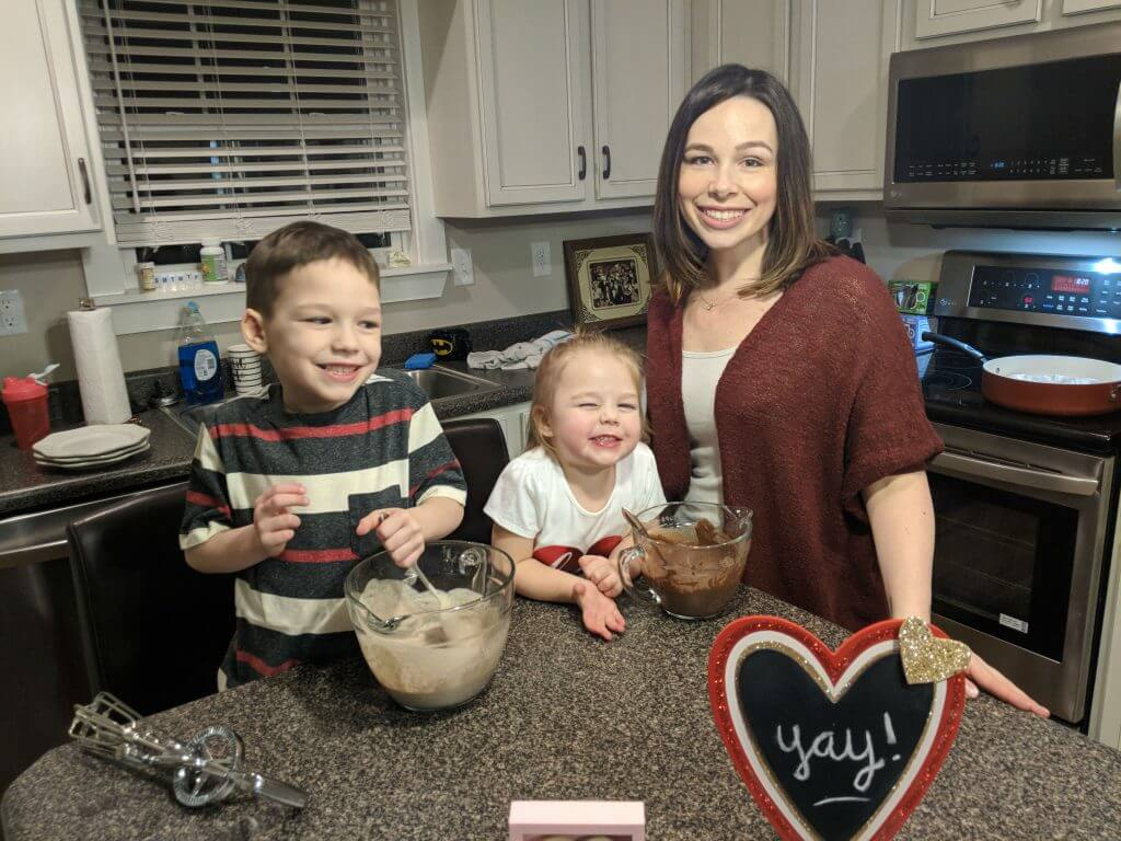 Christine, aka Bluegrass Blogger, stands at her kitchen counter with her young son and daughter. They are making healthy pancakes using a special Valentine's Day recipe. There are two mixing bowls filled with pancake batter on the counter in front of them. They are all looking at the camera and smiling.