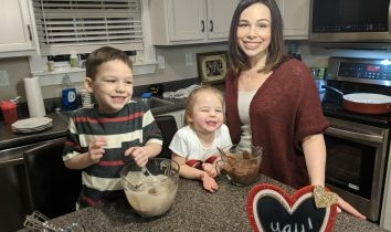 Bluegrass Blogger stands with her two children at the kitchen counter. They are all smiling at the camera. Two mixing bowls are in front of them, filled with pancake mix. They are making a Valentine's Day Recipe for Chocolate Cherry Pancakes.